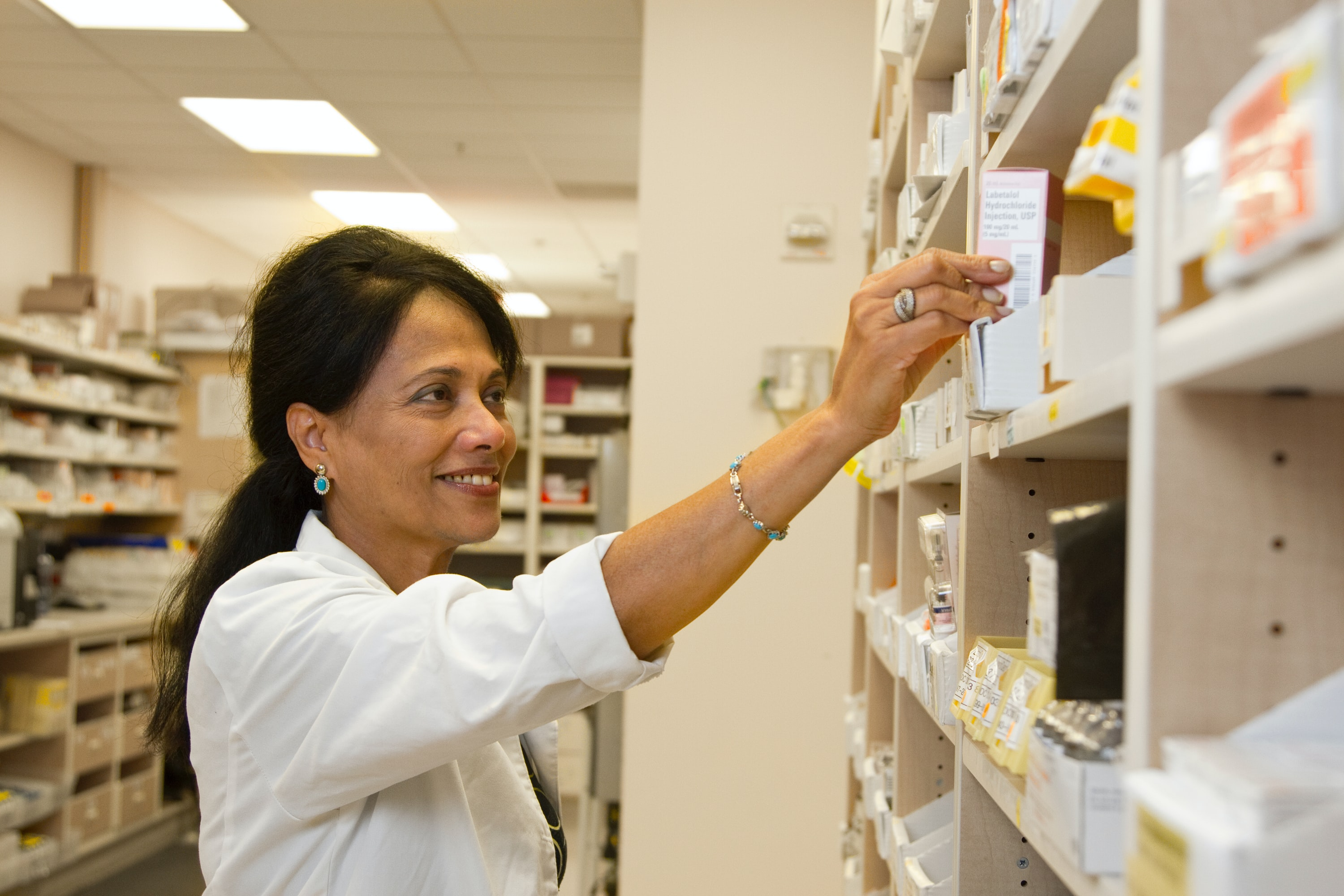 woman in white coat reaching into medical cabinet