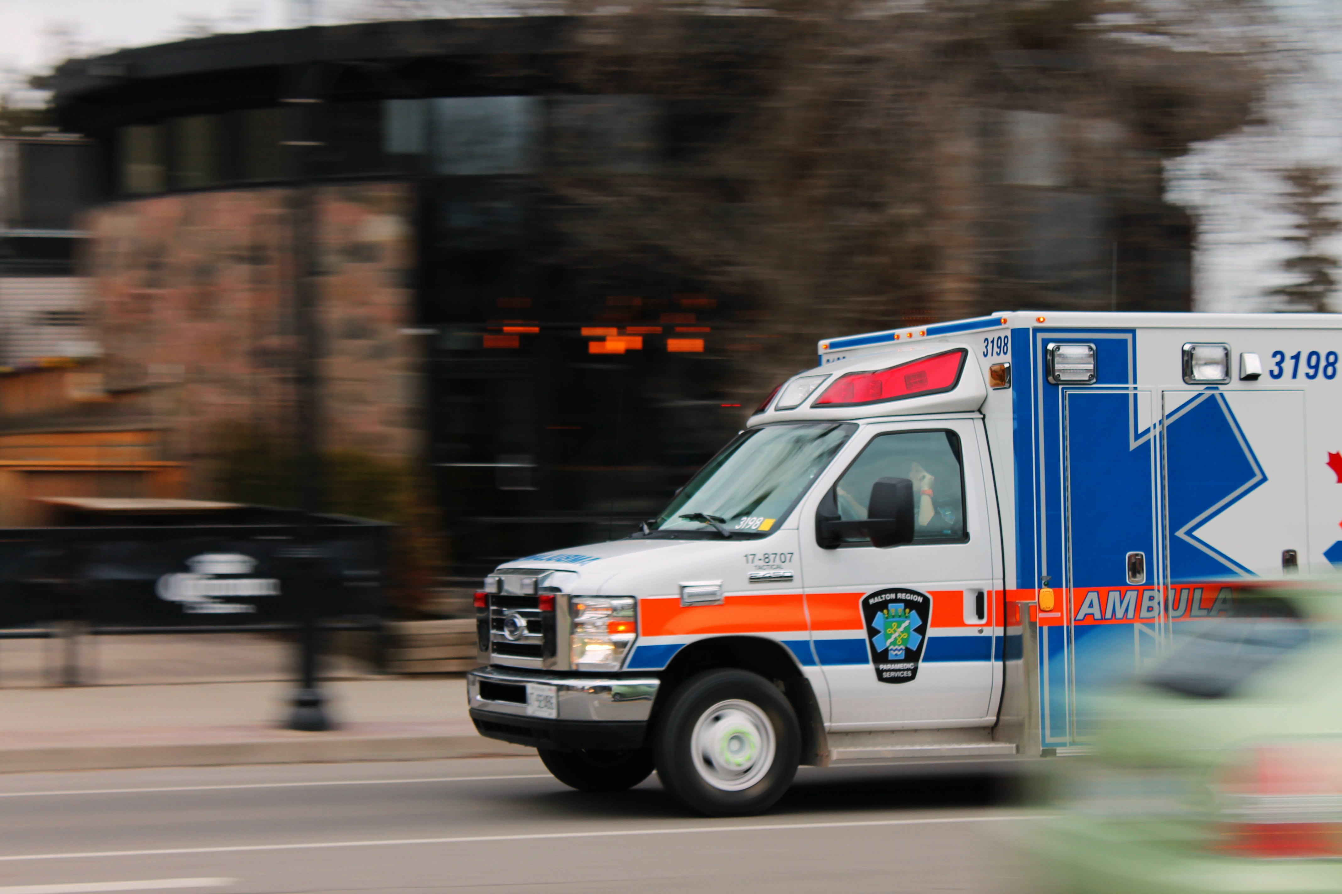 white and blue ambulance van traveling on road